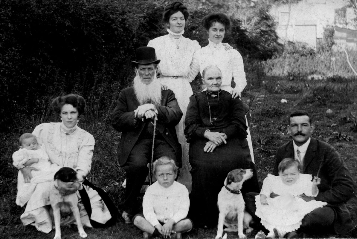 a family group with two old people, three young women, a man, three children and two dogs