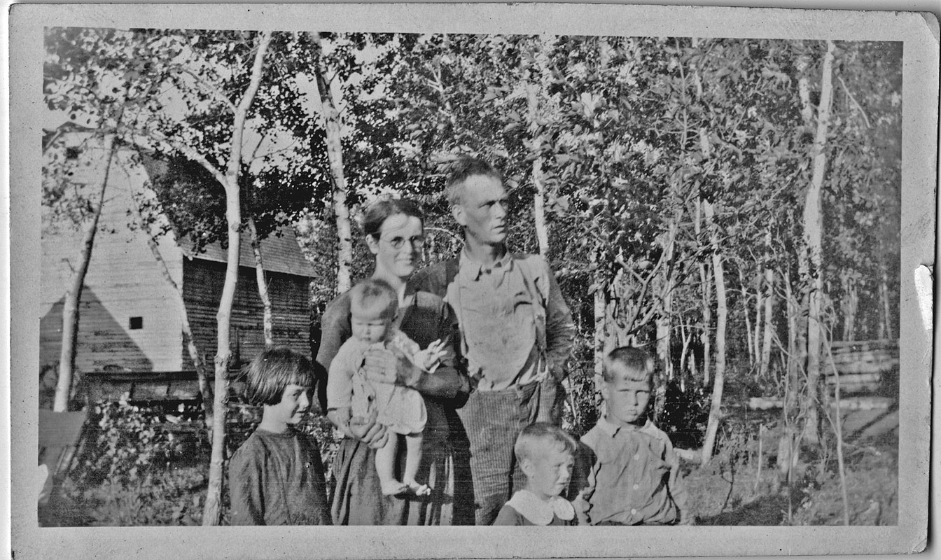 old photograph of family standing in forest beside wooden barn